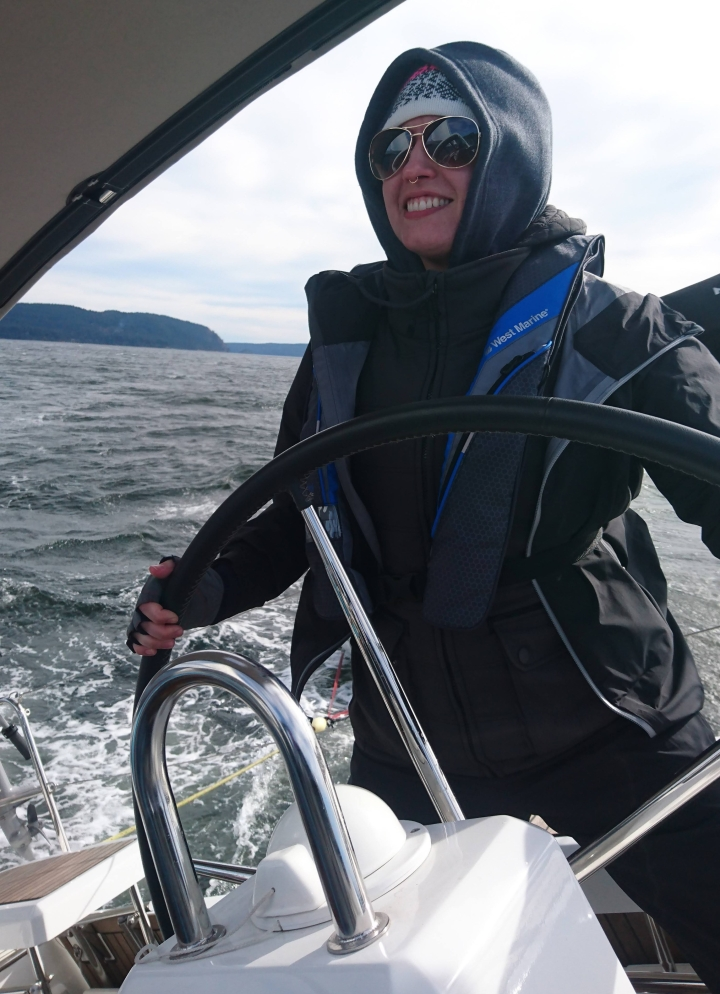 Photo of Celeste, a woman in sunglasses, at the helm of a sailboat
