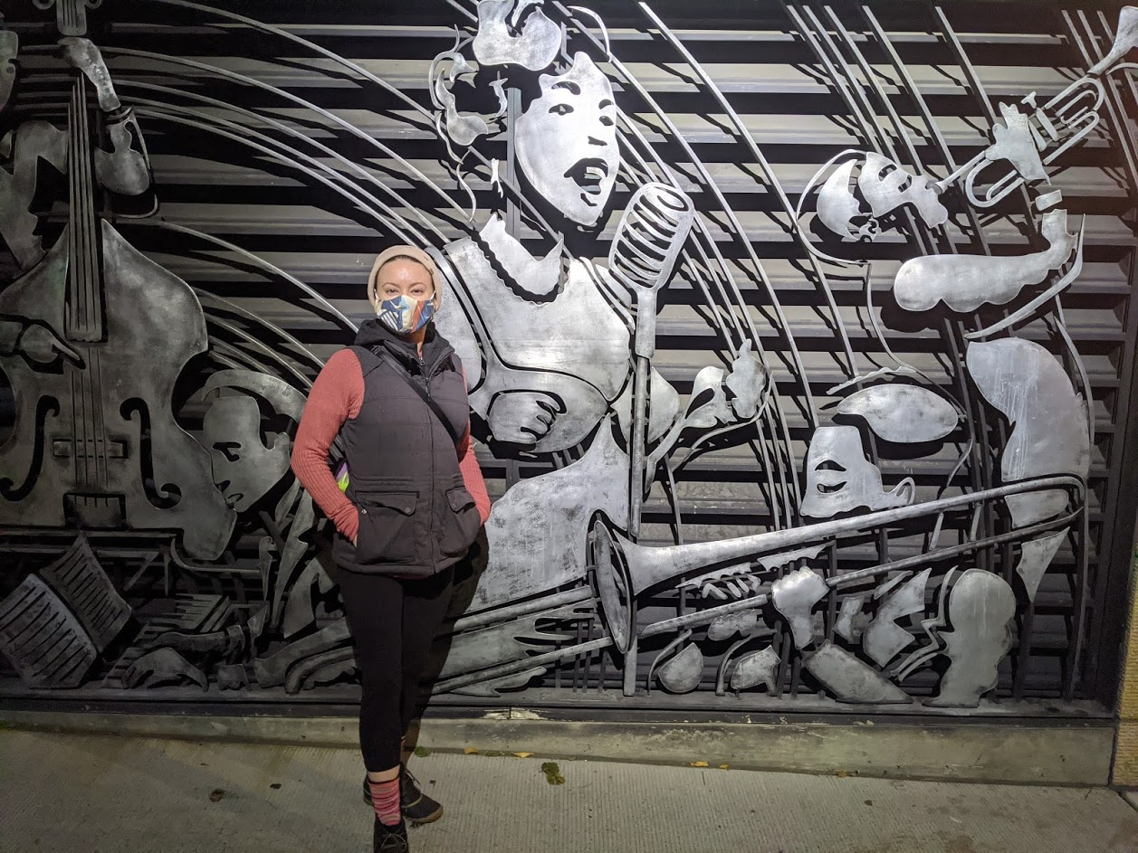 Celeste, a woman, standing in front of a silver metal mural art piece.